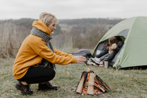 Donna di vista laterale che riscalda al fuoco Foto Gratuite