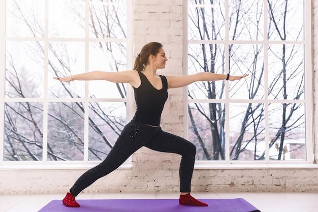 Donna di yoga che fa posa diritta di virabhadrasana nella stanza leggera sopra Foto Premium