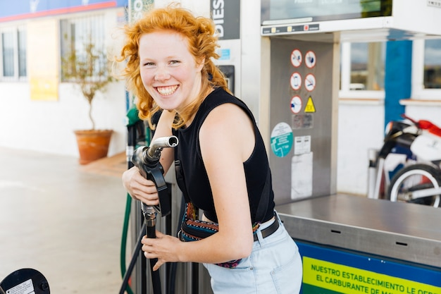 Donna divertendosi con la pistola di riempimento e sorridendo guardando la fotocamera Foto Gratuite