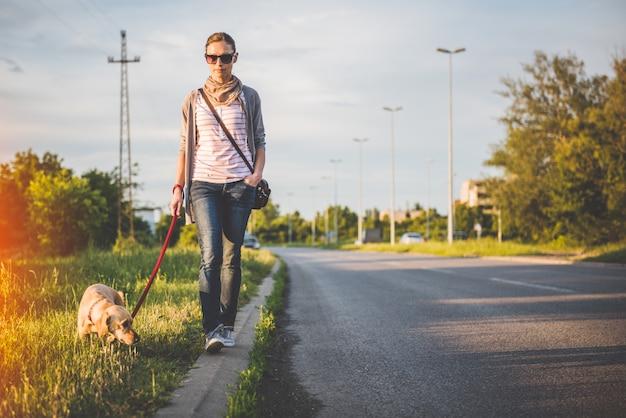 Donna e cane che camminano dalla strada Foto Premium