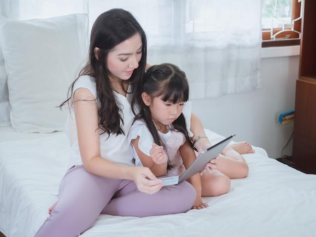 Donna e figlia che acquistano online con la carta di credito Foto Premium