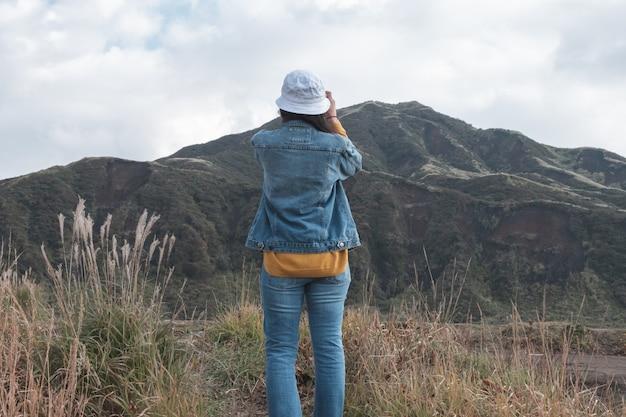 Donna e lanscape verde con sfondo di montagna aso, kusasenri, kumamoto, kyushu Foto Premium