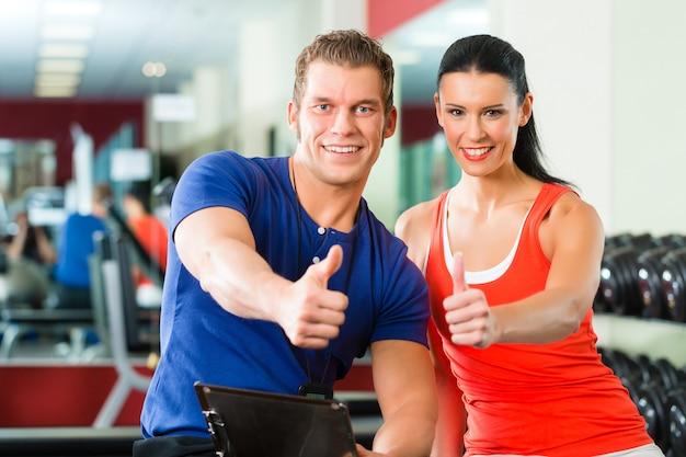 Donna e personal trainer in palestra con manubri Foto Premium
