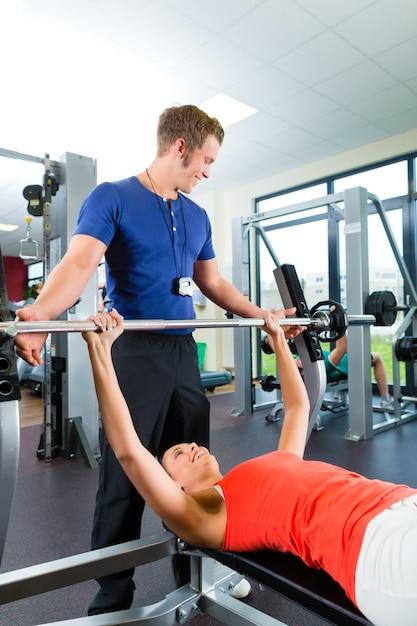 Donna e personal trainer in palestra Foto Premium