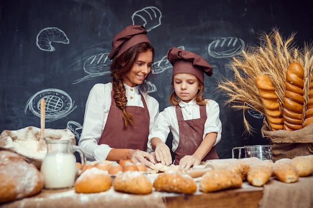 Donna e ragazza che producono insieme le pasticcerie Foto Premium