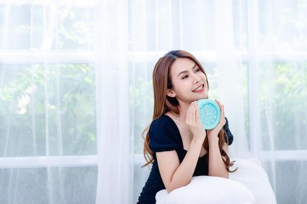 Donna e sveglia blu nella camera da letto rilassamento Foto Premium