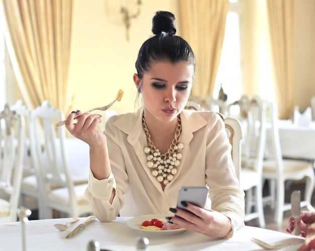 Donna elegante che controlla il suo telefono al tavolo Foto Premium