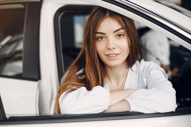 Donna elegante e alla moda in un salone di auto Foto Gratuite