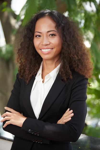 Donna esecutiva etnica felice che guarda l'obbiettivo Foto Gratuite