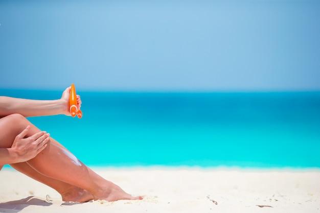 Donna esile che applica protezione solare sulle sue gambe, sedentesi sulla spiaggia sabbiosa con il mare Foto Premium