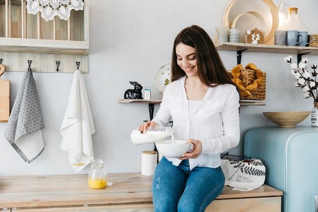Donna facendo colazione in cucina Foto Gratuite