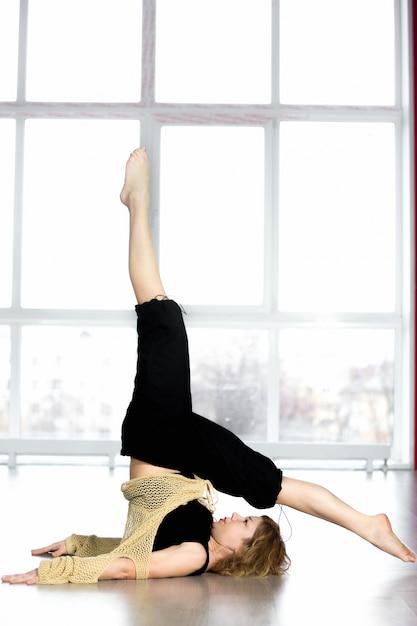 Donna facendo esercizi di equilibrio nella classe di yoga Foto Gratuite