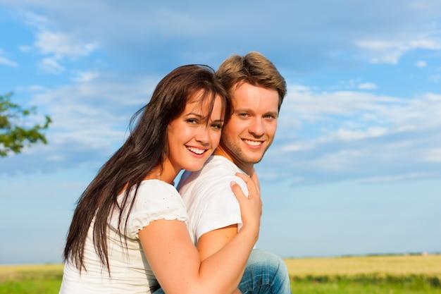 Donna felice che abbraccia il suo uomo nella natura Foto Premium