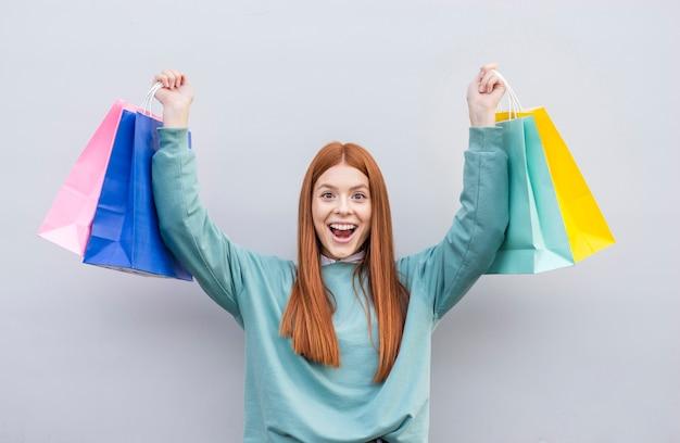 Donna felice che alza i sacchi di carta Foto Gratuite