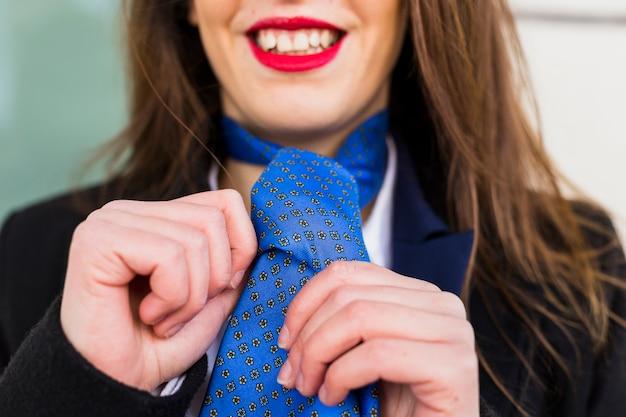 Donna felice che annoda cravatta blu Foto Gratuite