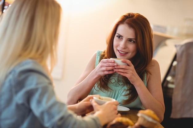 Donna felice che ascolta l'amico alla caffetteria Foto Premium