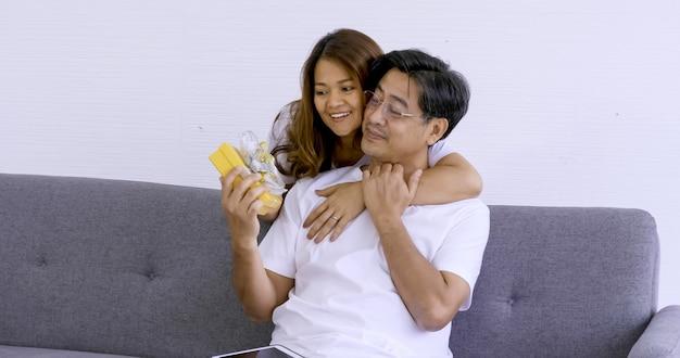 Donna felice che dà un contenitore di regalo giallo ad un uomo. Foto Premium