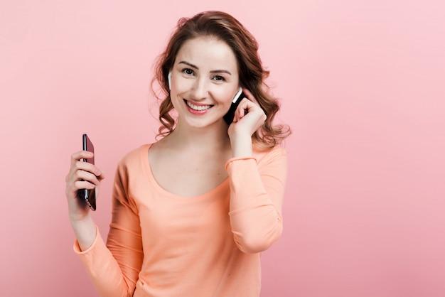Donna felice che gode della musica in airpods con la parete rosa Foto Premium