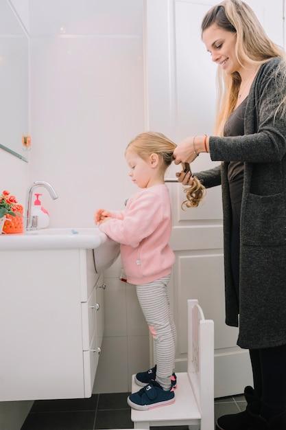 Donna felice che lega i capelli di sua figlia | Foto Gratis