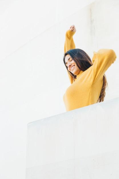 Donna felice che si estende al balcone Foto Gratuite