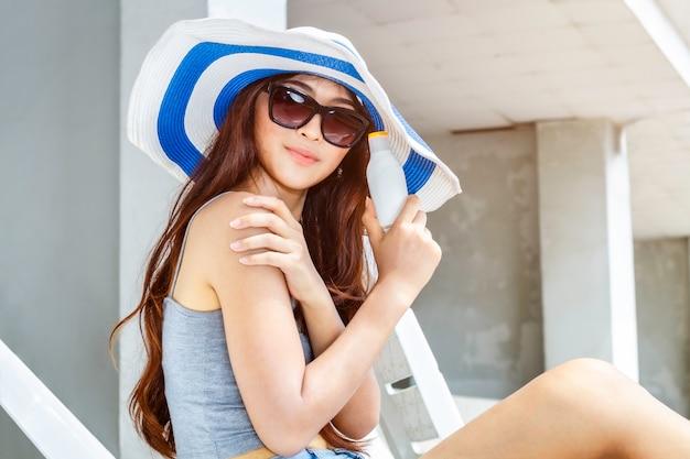 Donna felice che sorride in occhiali da sole che tengono cosmetico d'imballaggio della bottiglia della lozione della protezione solare della protezione solare. Foto Premium