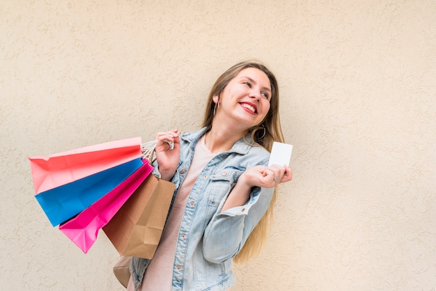 Donna felice che sta con i sacchetti della spesa e la carta di credito alla parete Foto Gratuite