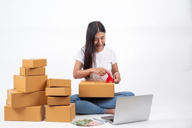 Donna felice chi sono le scatole di imballaggio nelle vendite online concetto di lavoro online Foto Gratuite