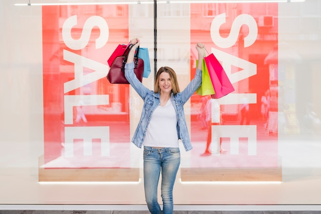 Donna felice con borse della spesa alzando le braccia Foto Gratuite