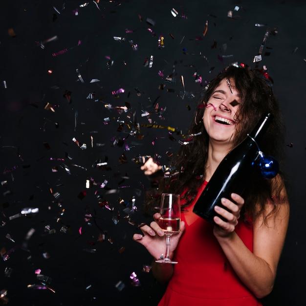 Donna felice con bottiglia di champagne e vetro Foto Gratuite