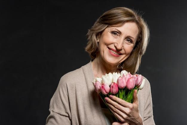 Donna felice con bouquet di fiori Foto Gratuite