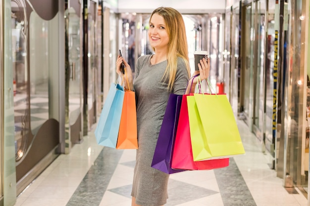 Donna felice con i multi sacchetti della spesa colorati che stanno nel centro commerciale Foto Gratuite