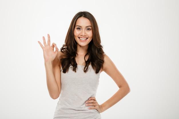 Donna felice del brunette con il braccio sull'anca che mostra segno giusto e che esamina la macchina fotografica sopra grey Foto Gratuite