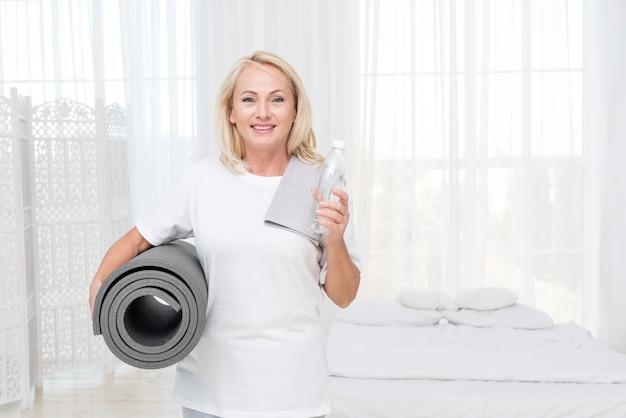 Donna felice del colpo medio con la stuoia di yoga e dell'acqua Foto Gratuite