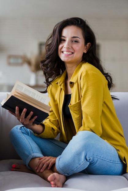 Donna felice della foto a figura intera che tiene un libro Foto Gratuite