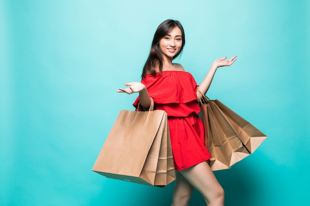 Donna felice di acquisto delle borse asiatiche della tenuta, isolata sulla parete verde. Foto Gratuite