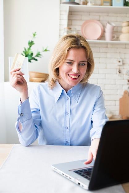 Donna felice di affari che per mezzo del computer portatile e della carta di credito Foto Gratuite