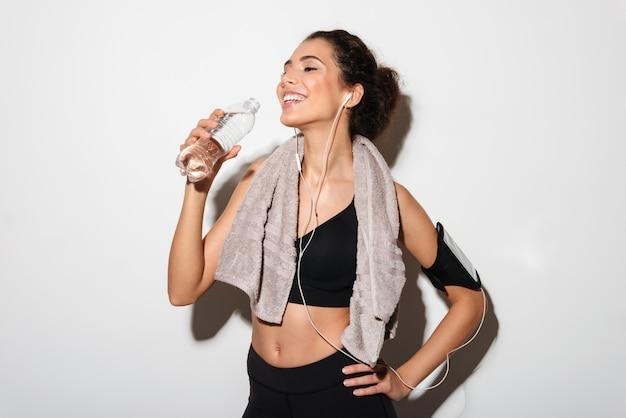 Donna felice di forma fisica del brunette con il braccio della holding del tovagliolo sull'anca Foto Gratuite