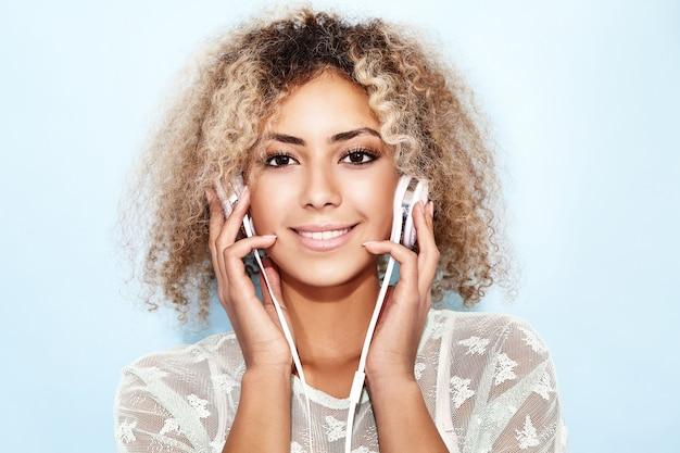Donna felice di modo con l'acconciatura afro bionda che sorride e che ascolta la musica in cuffie Foto Gratuite