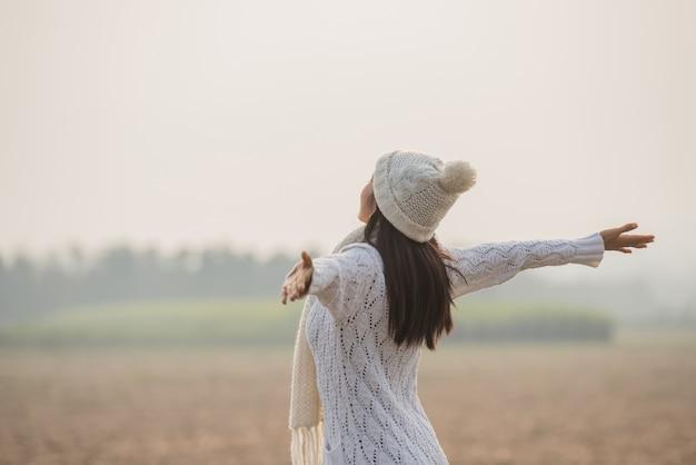 Donna felice godendo in natura idilliaca, celebrando la libertà e alzando le braccia Foto Gratuite