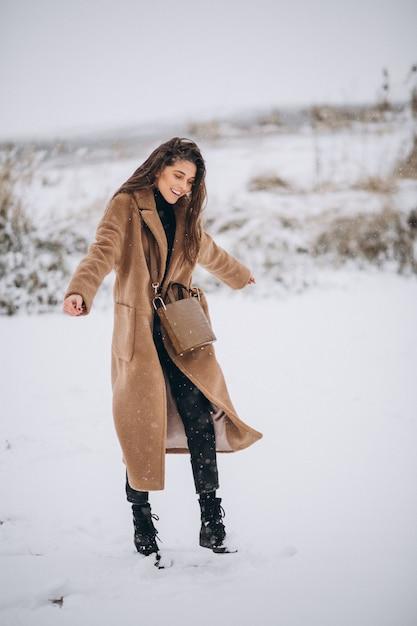 Donna felice in cappotto in inverno fuori nel parco Foto Gratuite