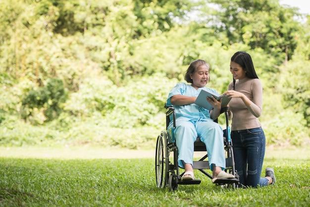 Donna felice in una sedia a rotelle che legge un libro con sua figlia al parco Foto Gratuite