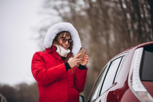 Donna felice parlando al telefono fuori in auto in inverno Foto Gratuite