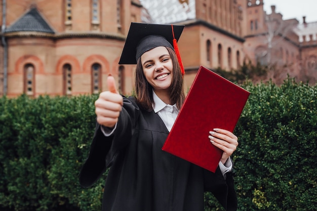 Donna felice per il suo giorno di laurea università. istruzione e persone. va bene segno Foto Premium