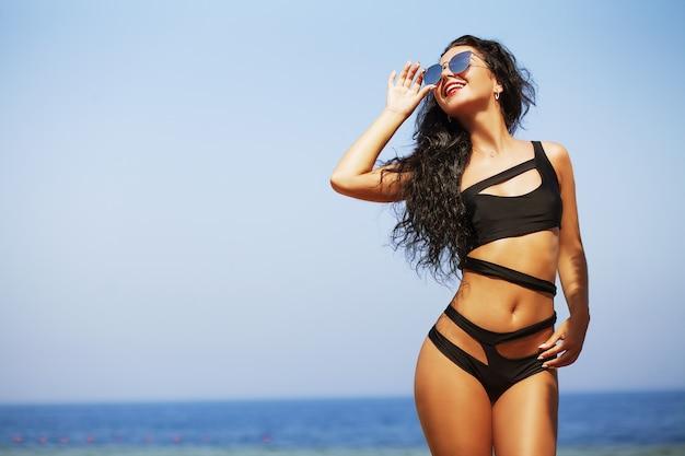 Donna felice sulla spiaggia Foto Premium