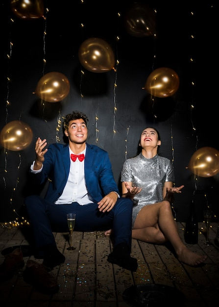 Donna felice vicino a uomo sorridente tra lancio di palloncini Foto Gratuite