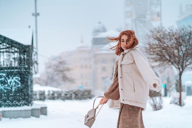 Donna fuori il giorno di inverno freddo di nevicata Foto Gratuite