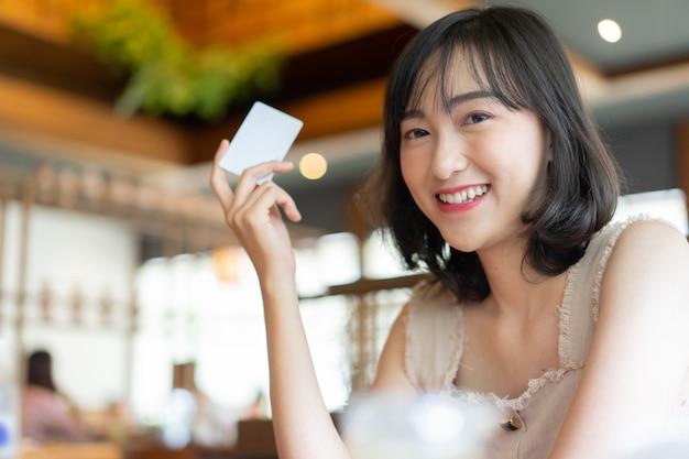 Donna giapponese che sorride e mano che mostra la carta di credito nel ristorante Foto Premium
