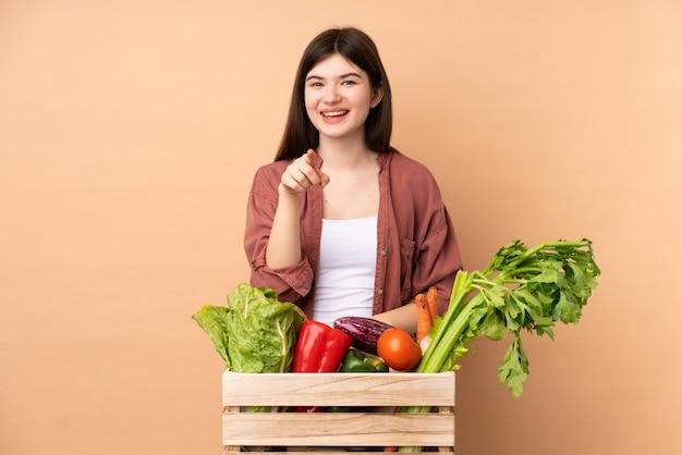 Donna giovane agricoltore con verdure appena raccolte in una scatola sorpresa e che punta davanti Foto Premium