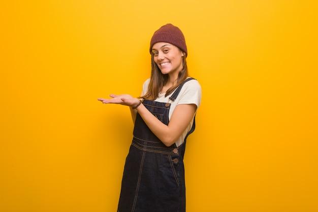 Donna giovane hipster che tiene qualcosa con le mani Foto Premium