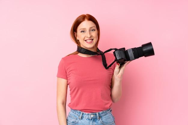 Donna giovane rossa su rosa isolato con una macchina fotografica professionale Foto Premium